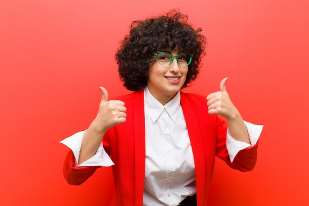 Młoda ładna afro kobieta uśmiecha się szeroko, szczęśliwy, pozytywny, pewny siebie i sukces