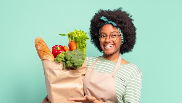 Młoda ładna afro kobieta wygląda na podekscytowaną i zaskoczoną, wskazując na bok i w górę, aby skopiować przestrzeń i trzymając torbę z warzywami