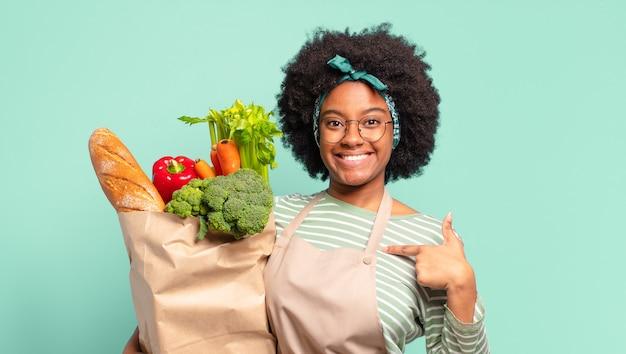 Młoda ładna afro kobieta wyglądająca na bardzo zszokowaną lub zaskoczoną, z otwartymi ustami, mówiąca wow i trzymająca worek z warzywami