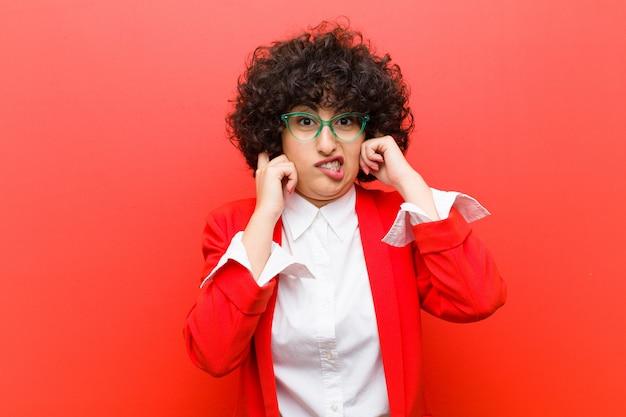 Młoda ładna afro kobieta, wyglądająca na złą, zestresowaną i zirytowaną, zakrywającą uszy ogłuszającym hałasem, dźwiękiem lub głośną muzyką