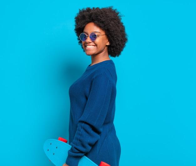 Młoda ładna afro kobieta z deskorolką