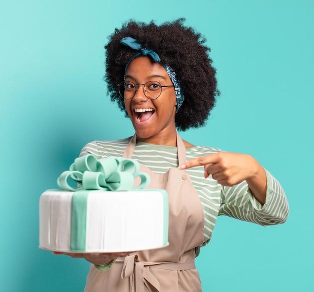 Młoda ładna afro piekarz kobieta z tortem urodzinowym