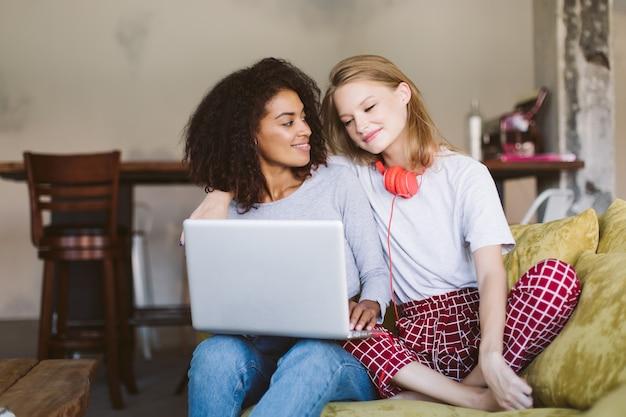 Młoda ładna afroamerykanka trzymająca laptopa na kolanach marzycielsko patrząc na uśmiechniętą kobietę o blond włosach i czerwonych słuchawkach w pobliżu, spędzając czas razem w domu
