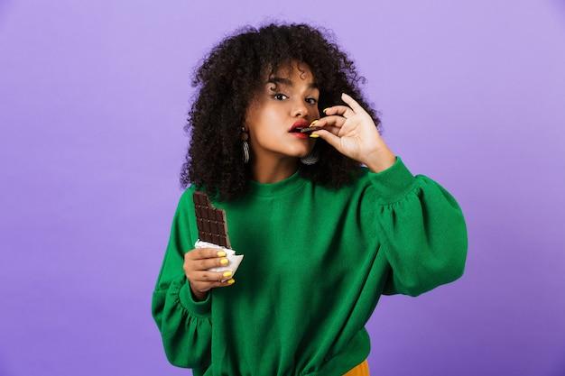 Młoda ładna afrykańska kobieta na białym tle nad fioletową przestrzeń je czekoladę.