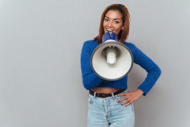 Młoda ładna afrykańska kobieta w swetrze i dżinsach rozmawia w megafonie i trzyma jedną rękę na biodrze. na białym tle szarym tle