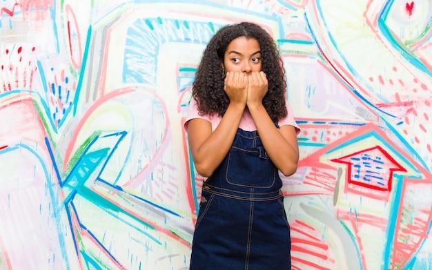 Młoda ładna amerykanin afrykańskiego pochodzenia kobieta patrzeje martwiący się przeciw graffiti ścianie