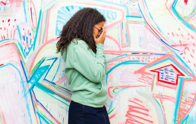 Młoda ładna amerykanin afrykańskiego pochodzenia kobieta zakrywa oczy z rękami z smutnym, sfrustrowanym spojrzeniem rozpaczy, płacze przy graffiti ścianie