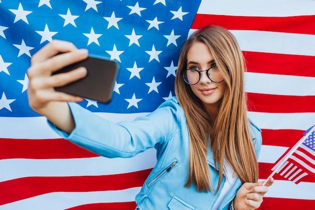 Młoda ładna amerykańska dziewczyna robi selfie z amerykańską flagę.