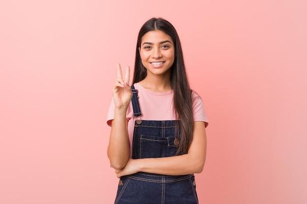Młoda ładna arabka ubrana w ogrodniczki dżinsów pokazuje numer dwa palcami.