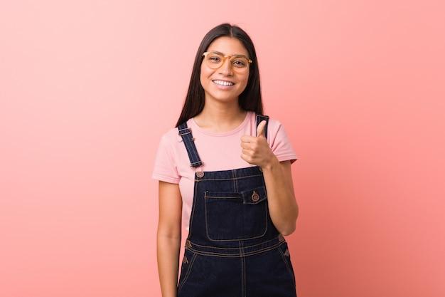 Młoda ładna arabka ubrana w spodnie jeansowe ogrodniczki, uśmiechając się i podnosząc kciuk do góry