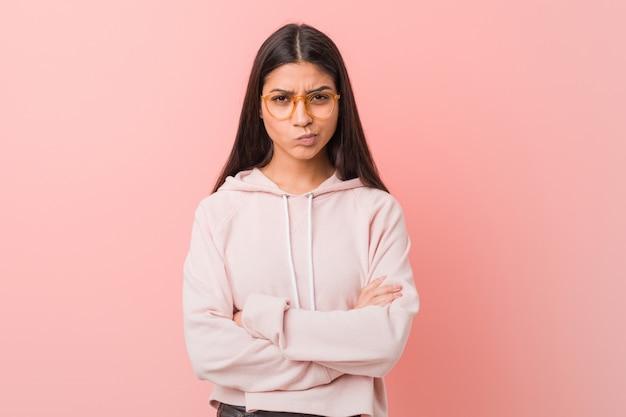 Młoda ładna arabska kobieta jest ubranym przypadkowego sporta spojrzenie marszczy brwi twarz w niezadowoleniu, utrzymuje ręki składać.