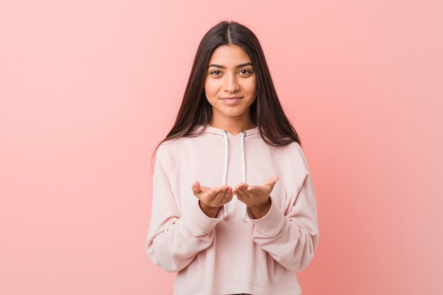 Młoda ładna arabska kobieta jest ubranym przypadkowego sporta spojrzenie trzyma coś z palmami