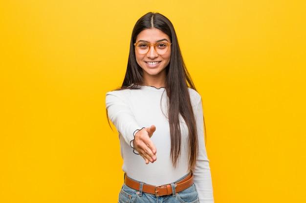 Młoda ładna arabska kobieta na żółtej rozciąganie ręce przy kamerą w powitanie gescie.