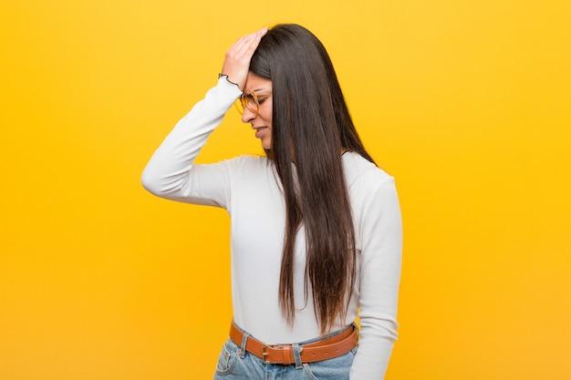 Młoda ładna arabska kobieta o żółtej ścianie zapominająca o czymś, uderzająca dłonią w czoło i zamykająca oczy.