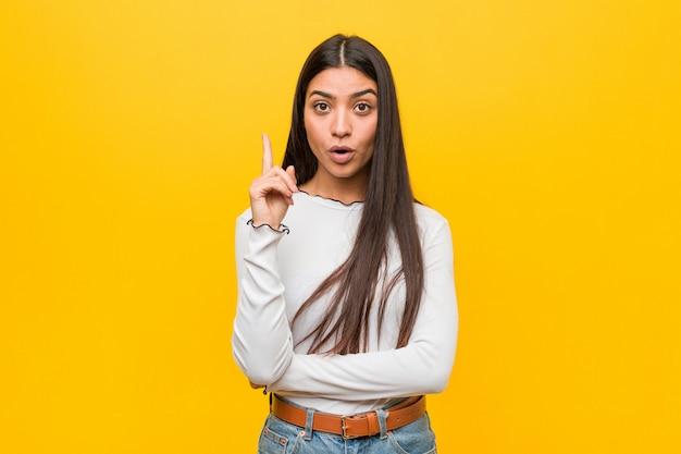 Młoda ładna arabska kobieta przeciw żółtej ścianie ma niektóre doskonałego pomysł, pojęcie twórczość.