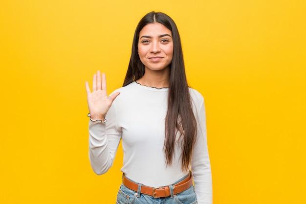 Młoda ładna arabska kobieta przeciw żółtemu ono uśmiecha się rozochoconemu seansowi liczba pięć z palcami.