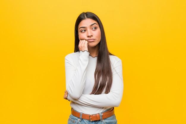 Młoda ładna arabska kobieta przeciwko żółtemu, która jest smutna i zadumana,.