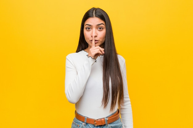 Młoda ładna arabska kobieta przeciwko żółtemu, trzymająca w tajemnicy lub prosząca o ciszę.