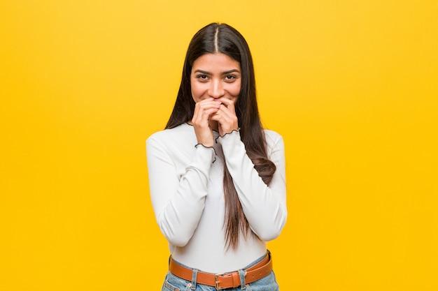 Młoda ładna arabska kobieta śmia się z czegoś na żółtym tle, zakrywający usta rękami.