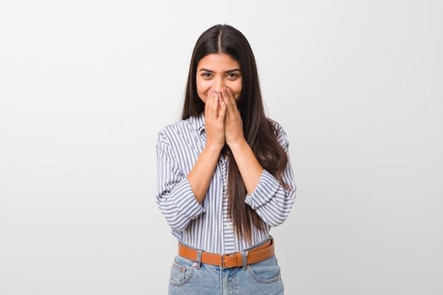 Młoda ładna arabska kobieta śmia się z czegoś, zakrywająca usta rękami.