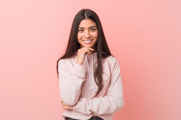 Młoda ładna arabska kobieta ubrana w sportowy styl wygląda uśmiechnięty szczęśliwy i pewny siebie, dotykając brody ręką.