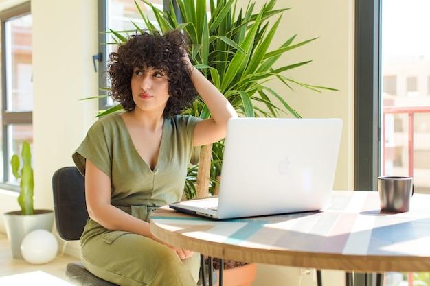 Młoda ładna arabska kobieta z laptopem na stole.