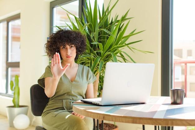 Młoda ładna arabska kobieta z laptopem na stole