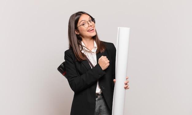 Młoda ładna architekt kobieta czuje się szczęśliwa, pozytywna i odnosząca sukcesy, zmotywowana, gdy staje przed wyzwaniem lub świętuje dobre wyniki