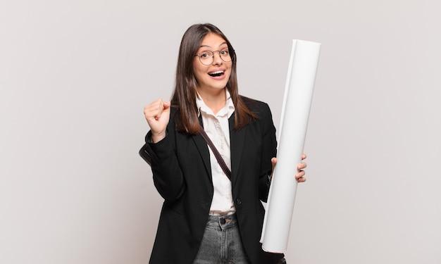 Młoda ładna architekt kobieta czuje się zszokowana, podekscytowana i szczęśliwa, śmieje się i świętuje sukces, mówiąc wow!