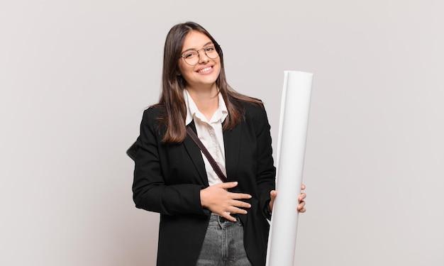 Młoda ładna architekt kobieta śmiejąca się głośno z jakiegoś śmiesznego żartu, szczęśliwa i wesoła, dobrze się bawiąca