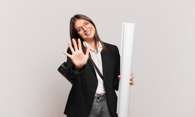 Młoda ładna architekt kobieta uśmiecha się i wygląda przyjaźnie, pokazując numer pięć lub piąty z ręką do przodu, odliczając w dół