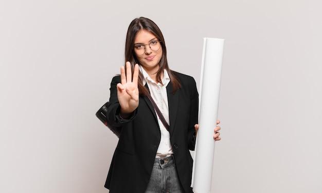 Młoda ładna architekt kobieta uśmiecha się i wygląda przyjaźnie, pokazując numer trzy lub trzeci z ręką do przodu, odliczając