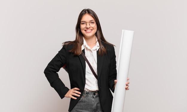 Młoda ładna architekt kobieta uśmiecha się radośnie z ręką na biodrze i pewna siebie, pozytywna, dumna i przyjazna postawa