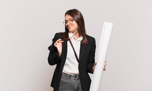 Młoda ładna architekt kobieta wyglądająca na arogancką, odnoszącą sukcesy, pozytywną i dumną, wskazującą na siebie