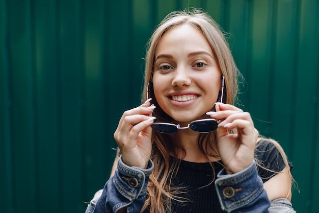 Młoda ładna atrakcyjna dziewczyna w drelichu odziewa w szkłach na prostej ciemnozielonej ścianie z miejscem na tekst.
