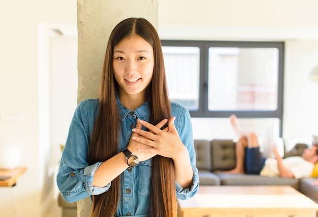 Młoda ładna azjatka czuje się romantycznie, szczęśliwa i zakochana, uśmiecha się radośnie i trzyma ręce blisko serca