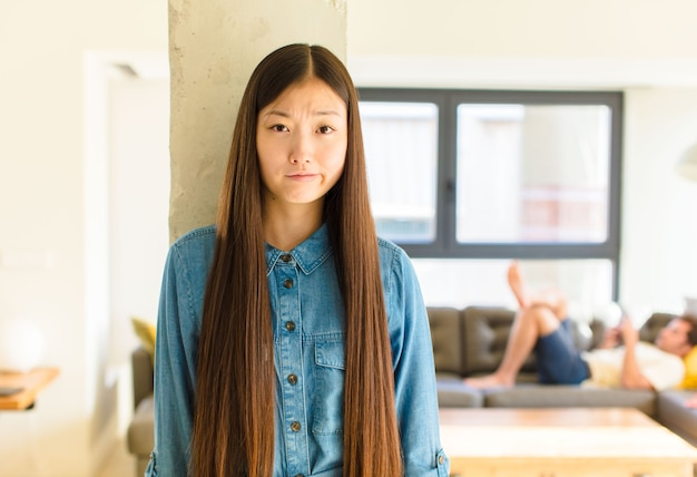 Młoda ładna azjatka czuje się zagubiona i niepewna, zastanawia się lub próbuje wybrać lub podjąć decyzję
