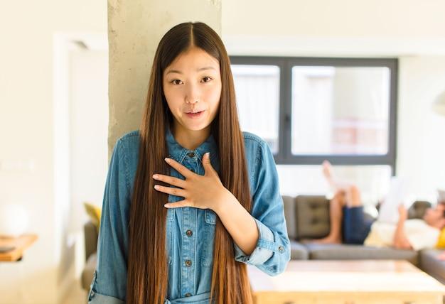Młoda ładna azjatka czuje się zszokowana i zaskoczona, uśmiecha się, bierze ręce do serca, jest szczęśliwa, że jest jedyną lub okazuje wdzięczność