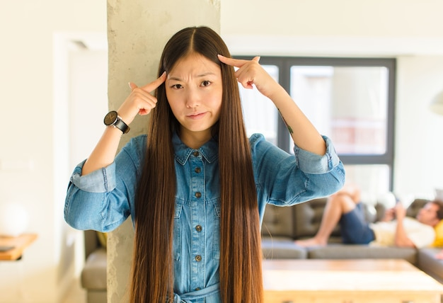 Młoda ładna azjatka o poważnym i skoncentrowanym spojrzeniu, burzy mózgów i myśląca o trudnym problemie