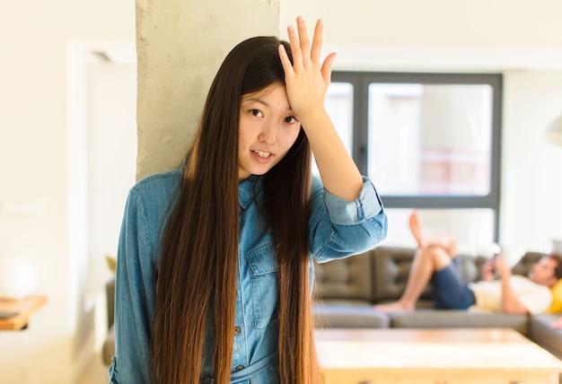 Młoda ładna azjatka podnosi dłoń do czoła i myśli o ups, po popełnieniu głupiego błędu lub przypomnieniu sobie, czując się głupio