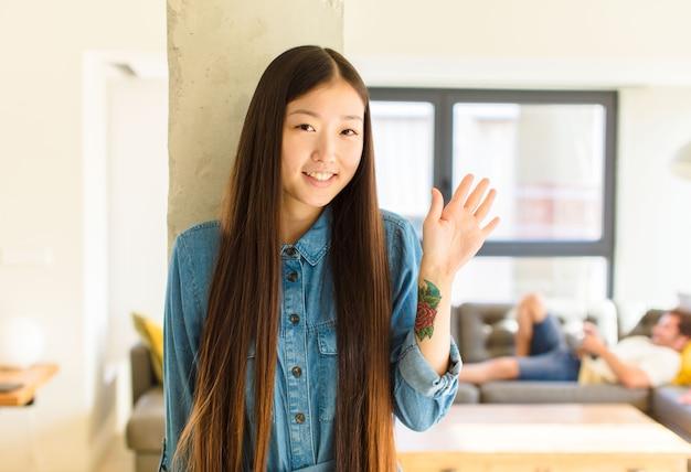 Młoda ładna azjatka uśmiecha się radośnie i wesoło, macha ręką, wita i wita lub żegna się