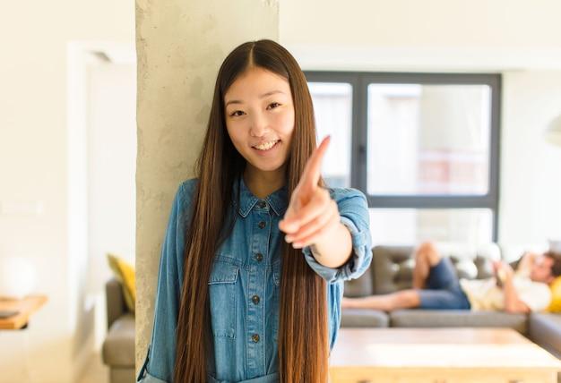 Młoda ładna azjatka, uśmiechnięta dumnie i pewnie, wykonująca triumfalnie pozę numer jeden, czując się jak przywódczyni