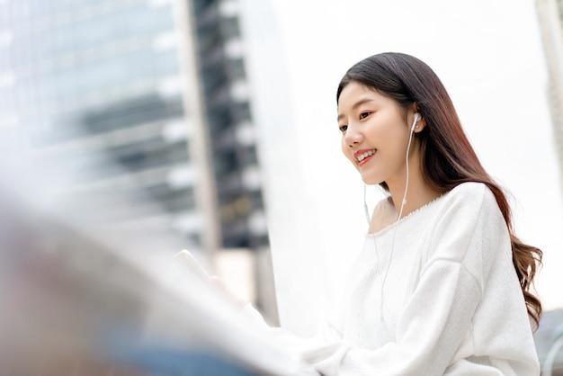 Młoda ładna azjatycka dziewczyna słucha muzyka na słuchawkach w mieście