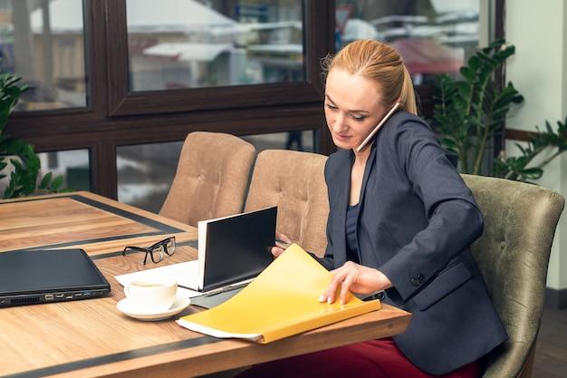 Młoda ładna biznesowa kobieta opowiada na telefonie i pracuje z dokumentami przy biurem.