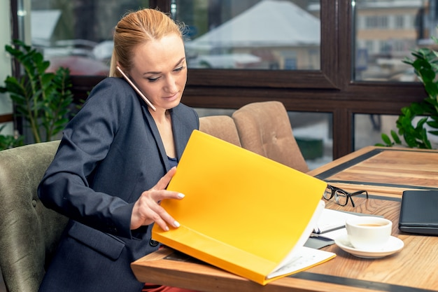 Młoda ładna biznesowa kobieta opowiada przez telefon i pracuje z dokumentami przy biurem.