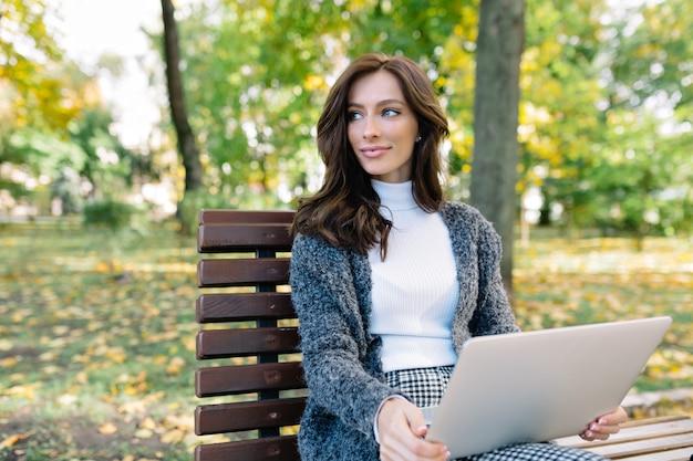 Młoda ładna biznesowa kobieta pracuje na laptopie na zewnątrz, inteligentna dama z uśmiechem patrząc na ekran. smartfon i okulary na stole. nosi stylową szarą kurtkę i białe zegarki.