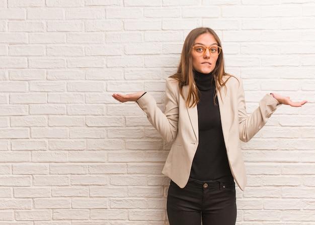 Młoda ładna biznesowa kobieta przedsiębiorca zmieszana i wątpliwa