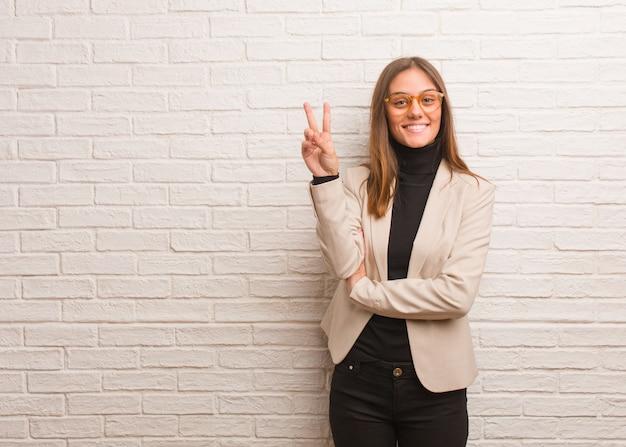Młoda ładna biznesowa przedsiębiorca kobieta pokazuje numer dwa