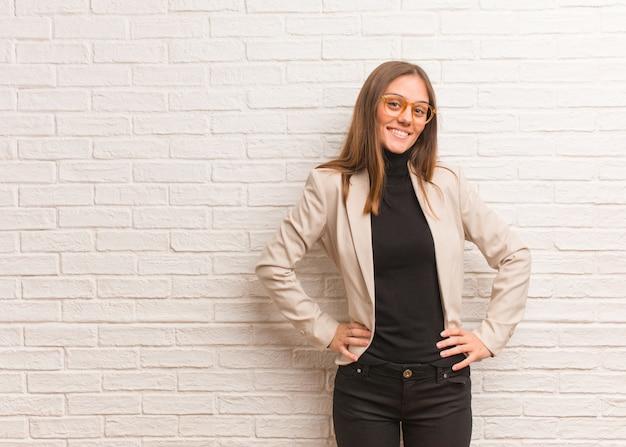Młoda ładna biznesowa przedsiębiorca kobieta z rękami na biodrach