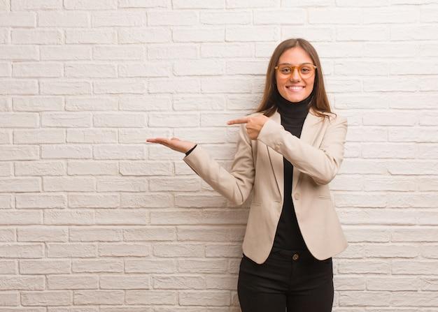 Młoda ładna biznesowa przedsiębiorcy kobieta trzyma coś z ręką